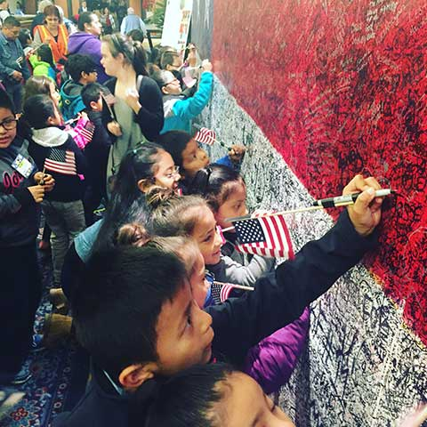 Children writing hero messages on Hometown Hero arriving at ArtPrize Seven