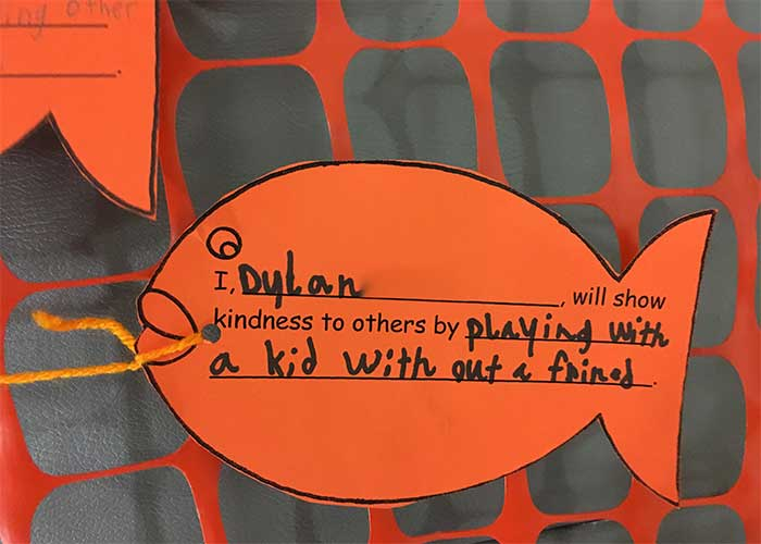 Elementary students participate in healing art by creating kindness promises on paper fish