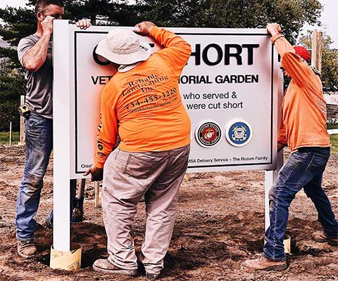 Workers installing Cut Short Veterans Memorial Garden sign during construction
