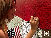 A young woman writes her hero message as the Hometown Hero canvas is getting very full during ArtPrize Seven