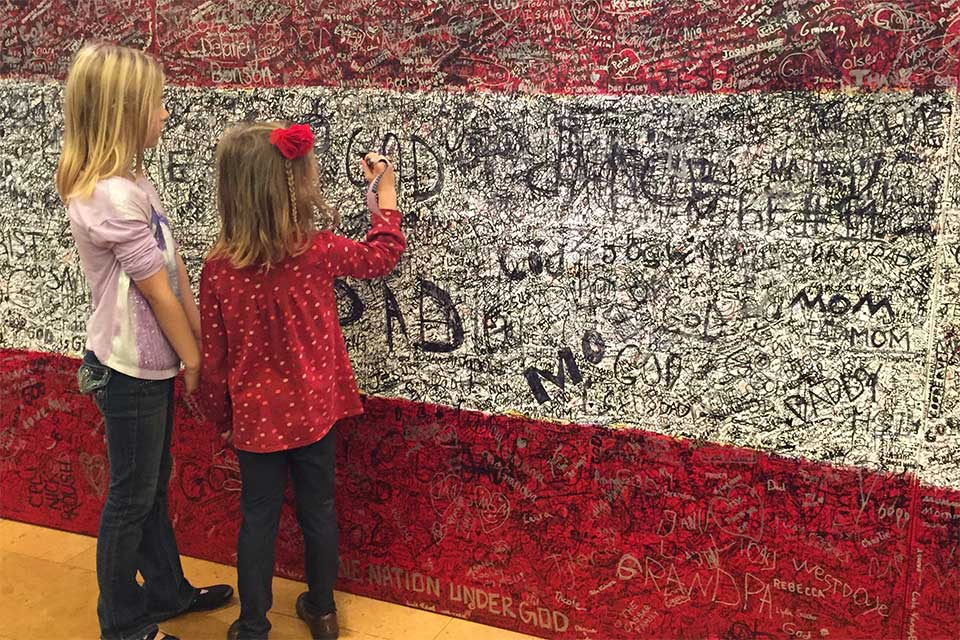 Young girls writing hero message on Hometown Hero painting
