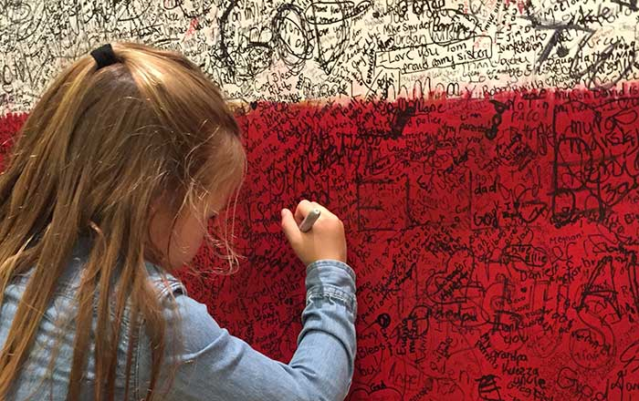 A young girl writing her hero message on Hometown Hero during ArtPrize Seven